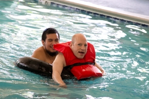 staff and Matt in red life jacket enjoying pool in fitness center